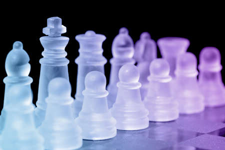 tactic: Chess pieces on check board with selective focus on king Stock Photo