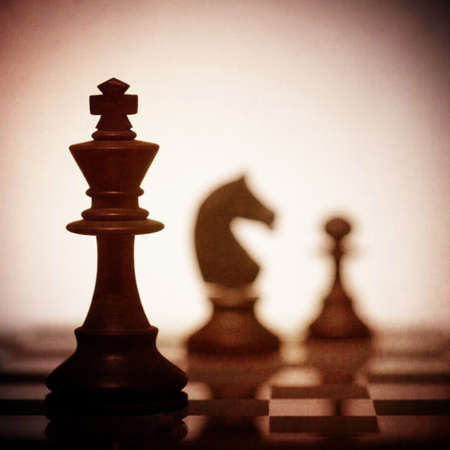 A close up of the King chess piece in silhouette with two other pieces in the background photo