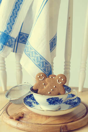 Homemade gingerbread men sitting in a vintage teacup  photo