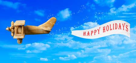 pull toy: Vintage volando el avión de juguete de madera en el cielo azul que tira de una bandera de fiesta feliz