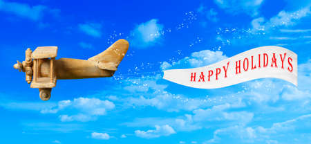 Vintage wooden toy plane flying in blue sky pulling a Happy Holidays banner  photo