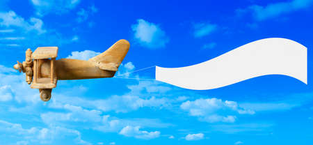Vintage wooden toy plane flying in blue sky pulling a blank white banner ready for your message photo
