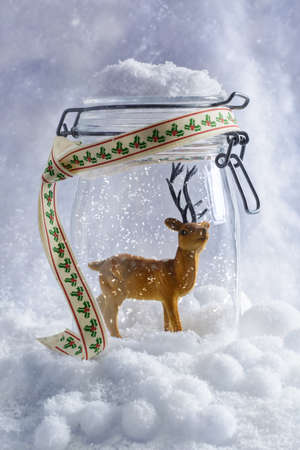 Reindeer figure in glass jar with falling snow photo