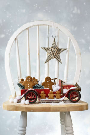 Festive Christmas gingerbread men sitting in vintage red truck with snow photo
