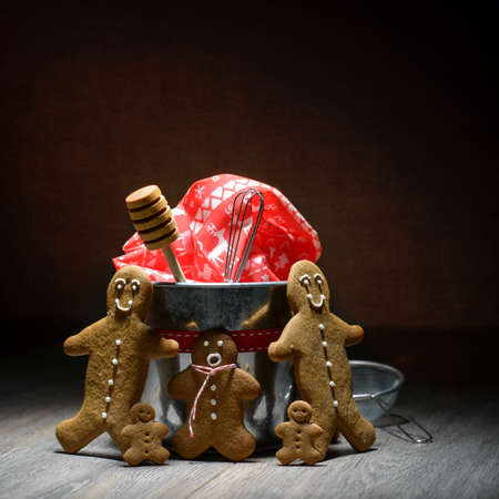 Low key image of homemade gingerbread family with baking utensils photo