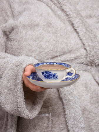 bath robes: Young woman holding a vintage blue and white teacup wearing a bathrobe