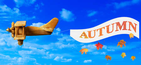 Vintage wooden toy plane flying in blue sky pulling a banner advertising autumn photo