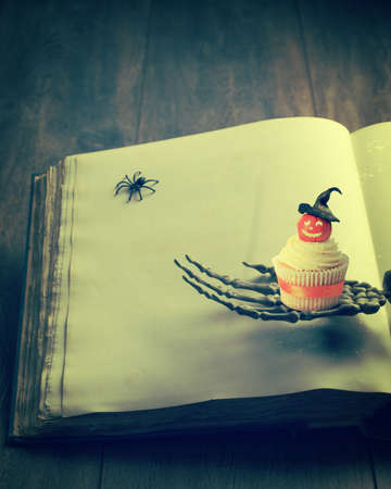 Cupcake for Halloween sitting on the hand of a skeleton against the pages of a book photo