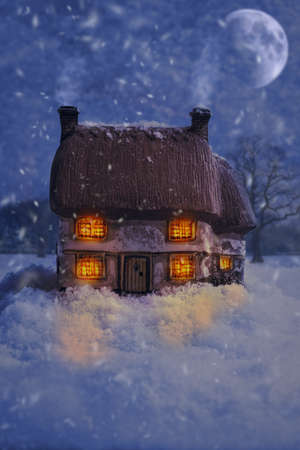 Cosy country antique ceramic cottage with falling snow Stock Photo - 32568418