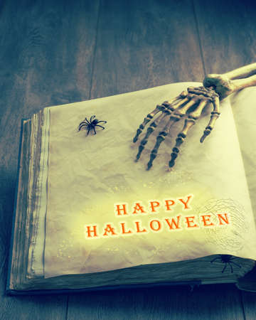 Happy Halloween with a skeleton hand over the pages of an old tomb photo