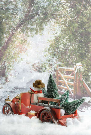Vintage red truck transporting Christmas trees in snowy country lane photo