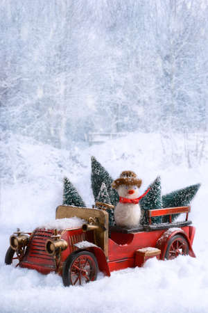 Vintage truck carrying Christmas trees in snow photo