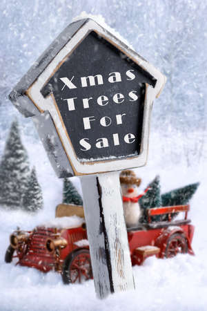 Christmas trees for sale sign with vintage red truck carrying trees in background photo