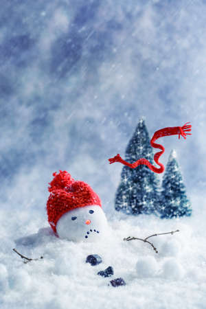 Snowman melting with scarf blowing away into Christmas trees Stock Photo - 33233904