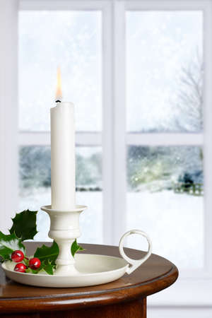 Christmas candle decorated with holly and berries against a winter window snow scene photo