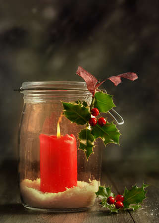 Red Christmas candle in glass jar with holly and berries photo