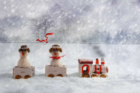 Christmas train set carrying snowmen, one with flying knitted scarf photo