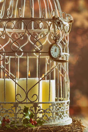 Pocket watch showing midnight on birdcage filled with candles photo