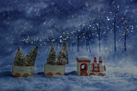 Christmas toy train set carrying trees at night