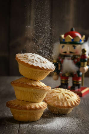 dusting: Dusting mince pies with icing sugar for Christmas Stock Photo