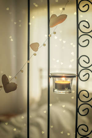 unmade: Lit candle with hearts against an unmade bed Stock Photo