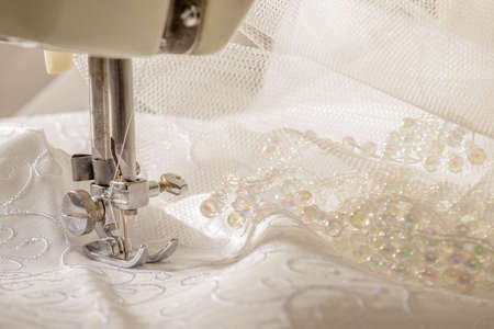 needle laces: Ivory wedding dress fabric being sewn on vintage machine Stock Photo