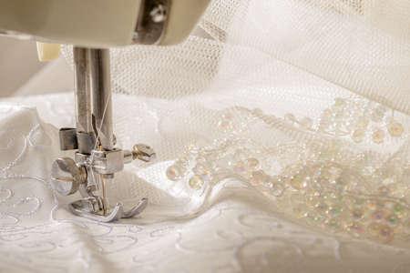 maquinas de coser: Tela del vestido de boda de marfil está cosiendo en la máquina de la vendimia