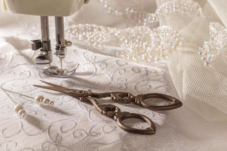 sew: Tijeras de coser antigua y materiales nupcial con la m�quina de coser Foto de archivo