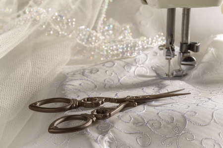 Antique scissors against wedding dress material and sewing machine