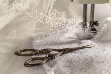 m�quina de coser: Tijeras antiguos contra material de vestido de novia y la m�quina de coser