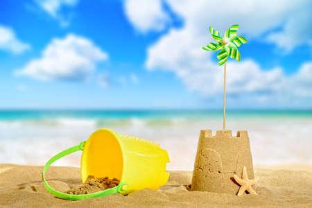Sandcastle on the beach with pinwheel