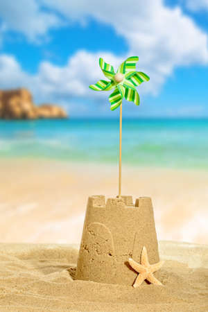 Sandcastle with pinwheel against a beach background photo