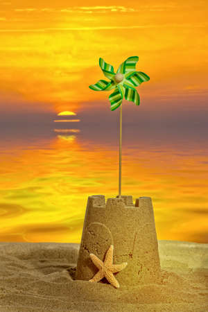 Sandcastle with windmill at sunset photo