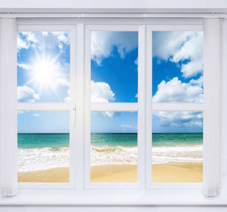 Beach house window overlooking an ocean view