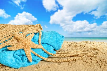 beach towel: Beach bag lying on sand with towel and starfish