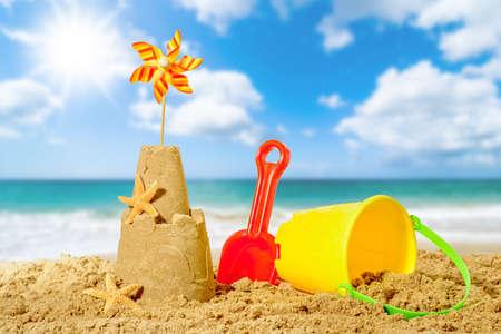 Castello di sabbia con secchiello e paletta con spiaggia sfondo sfocato