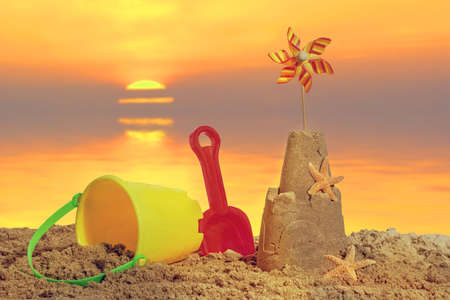 Sandcastle with bucket and spade on the beach at sunset photo