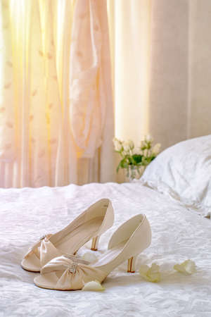 Brides sandals on the bed with wedding dress hanging in the background