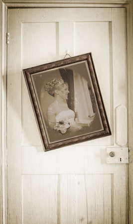 old photograph: Old photograph of bride in antique frame hanging on worn door