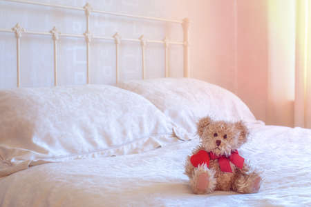romance bed: Teddy bear toy sitting on the bed holding a red heart