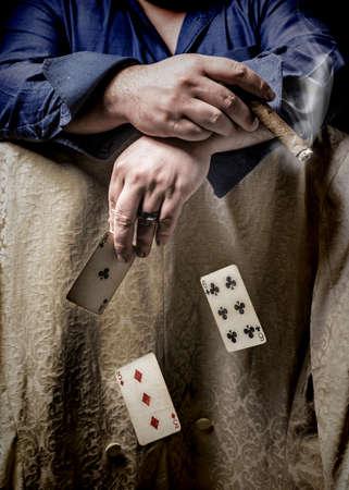 hombre fumando puro: Hombre que fuma un cigarro y jugar al póquer con la caída de las tarjetas