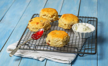 scones: Freshly baked scones on cooling rack with fresh cream and spoonful of strawberry jam