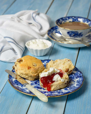 cream tea: Scones with jam and fresh cream on vintage plate with cup of tea in the background