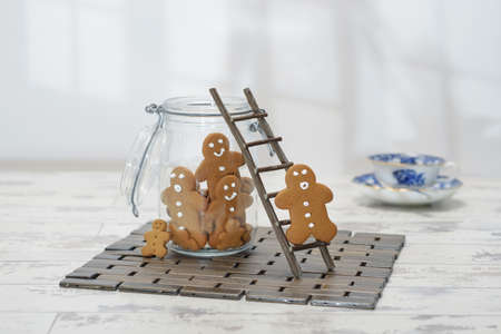 climbing ladder: Gingerbread man climbing ladder into cookie jar