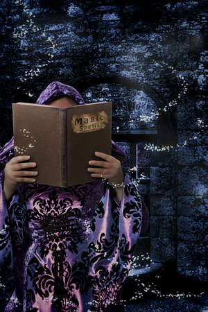 spells: Witch reading from a book of magic spells in the ruins of an abbey