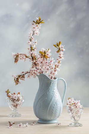 Antique pottery jug filled with blossom photo