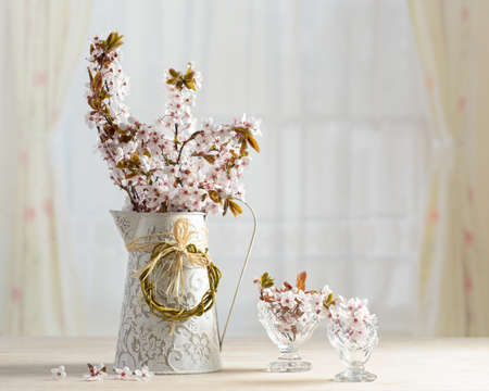 Springtime blossom in vase and antique glasses photo
