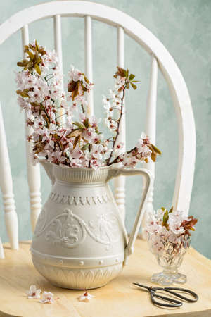 Spring blossom in antique pottery vase with scissors on rustic chair photo