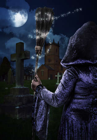 broomstick: Halloween concept with witch in graveyard with broomstick Stock Photo
