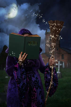 broomstick: Woman wearing purple cloak in graveyard with book of magic spells and broomstick Stock Photo